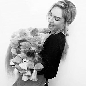 stephanie holding pile of blond russian hair wefts black and white image